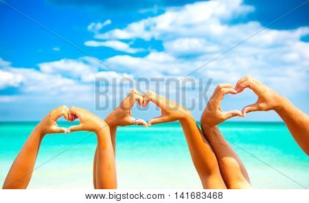 Summer holidays concept. Beautiful Happy young family father, mother and little son making heart shape with their hands over sea background. Tanning together. Vacation concept. Tourism