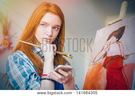 Thoughtful attractive young readhead woman painter thinking and holding cellphone in artist workshop