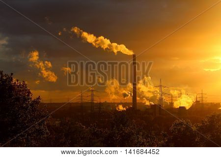 A power plant with a high chimney releasing white smoke and with an electrical line at the background at a mild-coloured sunset