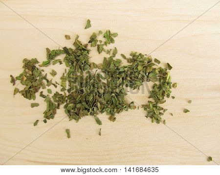 Dried lovage leaves on wooden board for cooking