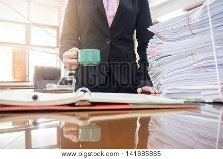 Business woman holding coffee cup in office