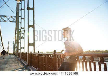 Concentrated young handsome sports man resting after running while leaning against bridge railing