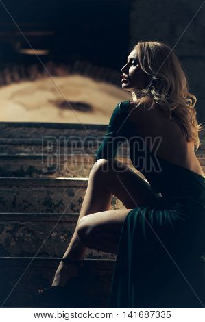 Young woman with blonde hair dressed in sensual green gorgeous dress with bare back beautiful legs sitting on stairs on dark background indoor