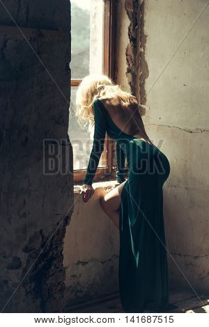 Young woman with blonde hair dressed in green sexi dress with bare back posing near old window indoor