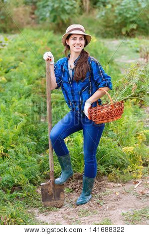 autumn harvesting concept. Happy smiling caucasian female farmer or gardener holding spade and basket of harvested vegetables . Woman working in the garden