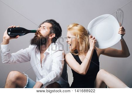 young family couple in quarrel of blonde pretty girl with kitchen utensils and bearded man with long beard holding wine bottle sitting on bathtub. household everyday life and routine