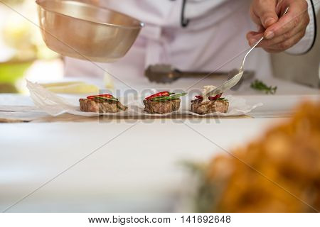 Pieces of cooked meat. Male hand with a spoon. Delicious medallions with roquefort sauce. Dinner for a gourmet.