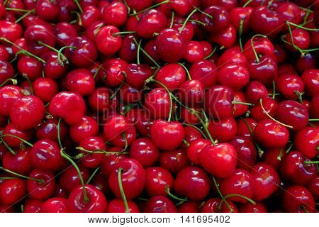 Background image with many red cherries for sale in a market