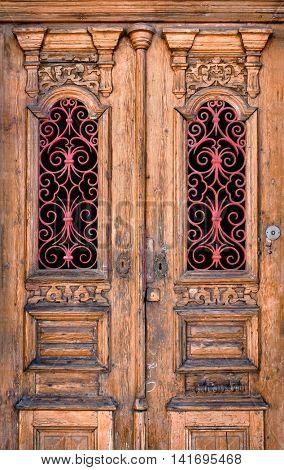 Double wooden door detail with red decorative ironwork in windows