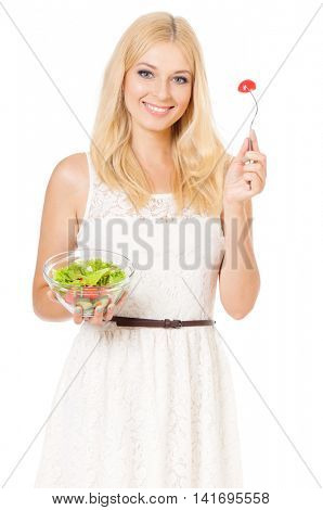 Half-length portrait of very beautiful woman eating fresh salad and looking at us. Smiling young housewife with green vegetables. Studio shot isolated on white background. Healthy eating concept.