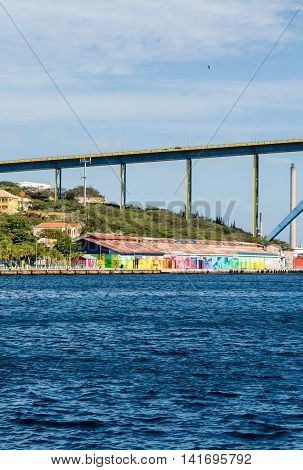 Colorful buildings in Curacao under the blue sky bridge