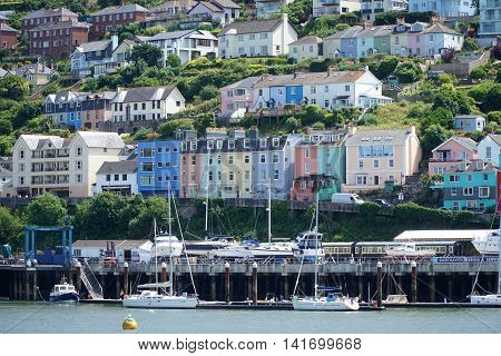 DARTMOUTH, UK - JULY 6: Colourful houses line the river front of the small English hillside village of Kingswear, Devon, opposite the tourist town of Dartmouth on the estuary of the River Dart. on July 6, 2016.