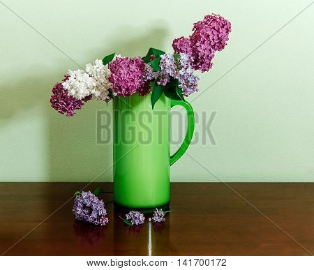 Two Branch of White and Purple Lilac in the Green Plastic Pitcher.Wooden Table