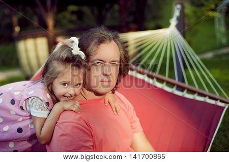 Happy family father and daughter relax in the summer outdoors in the Park in a hammock cheerful girl hugged from behind by the shoulders