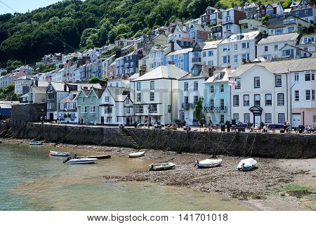 DARTMOUTH, UK - JULY 6: People sit and walk on the riverside promenade in the popular tourist town of Dartmouth, in Devon, south-west England on July 6, 2016.