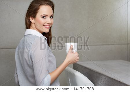 A woman sitting on the couch with a cup in her hands and smiling