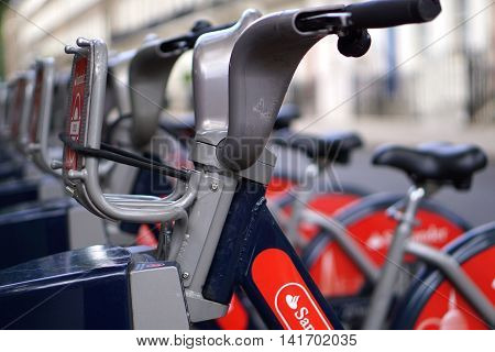 LONDON, UK - JULY 25: Rental bikes line a roadside in central London on July 25, 2016. The bicycles are part of the Santander Cycles public hire scheme, popularly known as Boris Bikes.