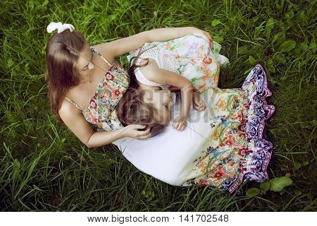 Mother and daughter in a beautiful floral sundresses in the summer sit on grass and hug. The girl clung to a pregnant woman and listens to her tummy. The view from the top