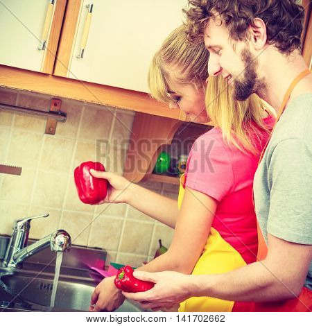 Couple Washing Fresh Vegetables In Kitchen