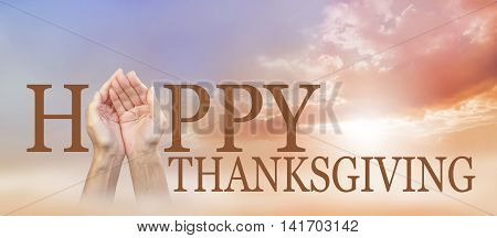 Sharing a Happy Thanksgiving -  wide autumnal sunset sky background with a pair of cupped female hands making the A of HAPPY with THANKSGIVING below and copy space above