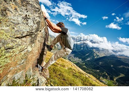Adult man climbs on a big stone, against a blue sky and valley with Zermatt town