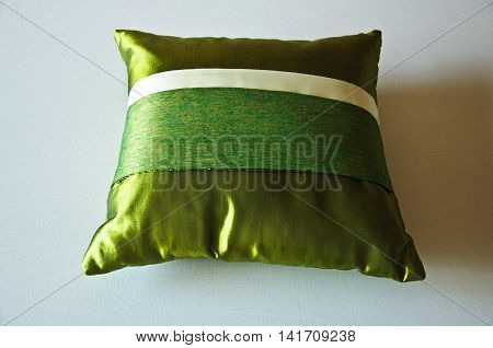 green silk bright pillow on bed, top view