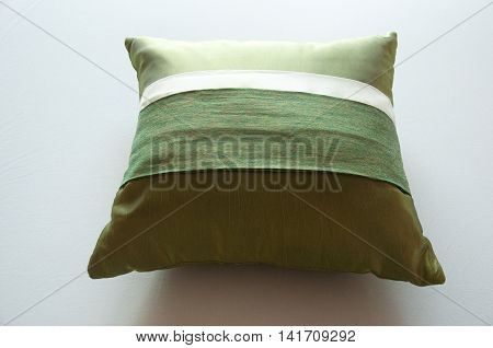 Decorative pillow on white bed, green pillow