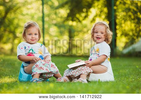 The two little baby girls two-year old sitting on pots against green grass