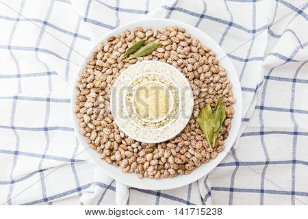 three kinds of uncooked rice and beans in porcelain bowls on a dishcloth