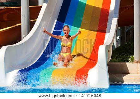 Happy young girl on water slide at water park show thumb up. Water slides with flowing water in aqua park. Summer water park holiday. Outdoor.