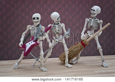 A Skeleton in a skeleton band playing broom as guitar