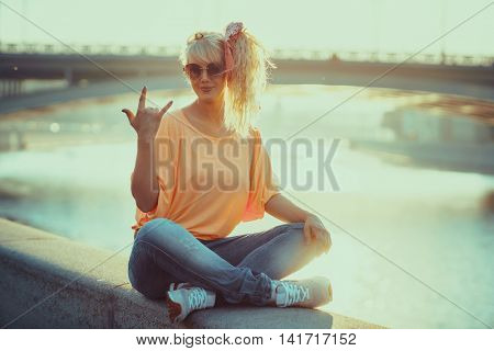 Young teenage style woman sitting on stone quay at morning sunrise.
