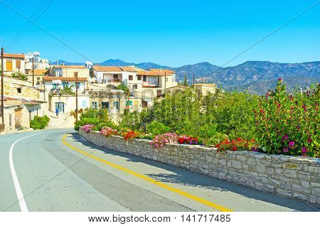 The mountain intercity road along the Kato Drys village neighbors with the scenic gardens full of lush trees and colorful flowers Cyprus.