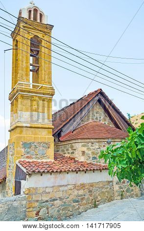 The slender bell tower of St George Church was built of the bright yellow stone Gourri village Cyprus.