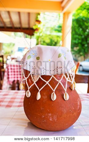 The crock with wine covered with the handmade napkin decorated with lace embroidery and seashells Gourri village Cyprus.
