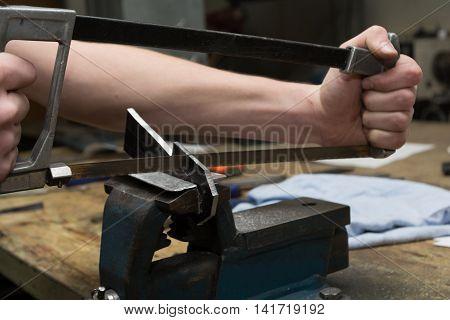 Hacksaw with metalworking in use - closeup craftsmen