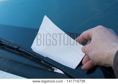 Ticket is stapled by park rangers on windscreen - closeup