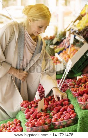 woman looking at strawberries at a fruit stand