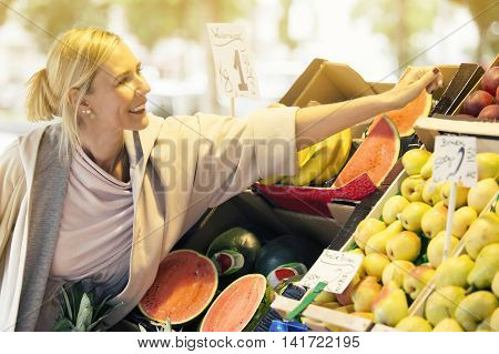 blond woman standing at fruit stand and picking apples