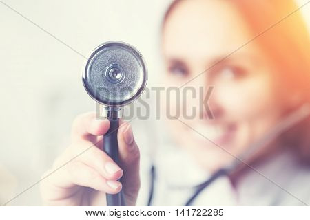 Smiling doctor holding phonendoscope blurred look. Concept of medical help.Toning filter