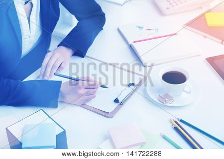 Businesswoman sitting at table and making notes. Notebook and cup in front of her. Only hands seen. Office. Concept of work.Film effect