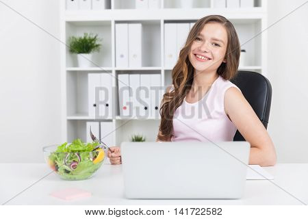 Woman is eating salad near her laptop in white office. Bookcase with binders at background. She is smiling. Concept of healthy food and lifestyle.