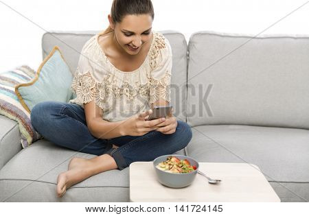 Woman sitting on the couch ready to eat and talking picture to her food