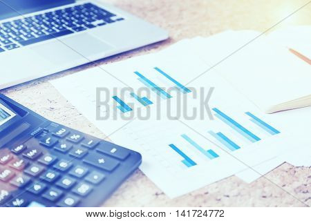 Closeup of cork table with keyboard calculator business report and blank copybook with pen. film effect