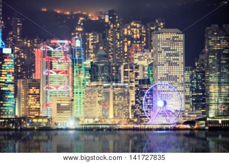 Hong Kong island central quay with observation wheel during laser show from Victoria's harbour. Defocused glowing night abstract shot