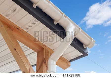 SIP panel house construction. New white rain gutter. Drainage System with Plastic Siding Soffits and Eaves against blue sky