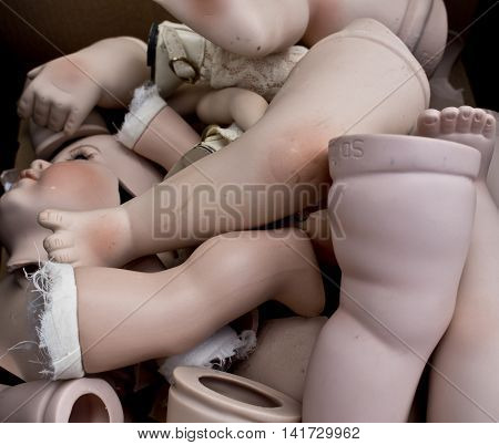 Doll hands, legs, face, feet, parts piled