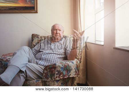 Indoor shot of a caucasian senior man sitting at assisted living facility. Elderly man sitting on an arm chair by the window at home.