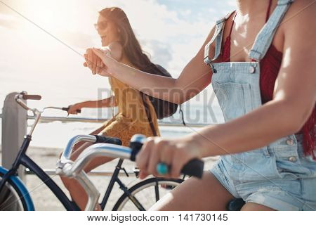 Two Female Friends Holding Hands And Riding Cycles