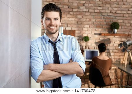 Portrait of happy smiling confident businessman standing against wall.